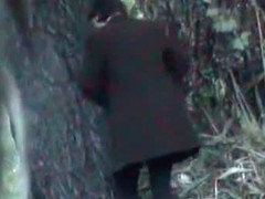 A business woman goes to take a piss in the autumn forest