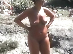 Nudist camp at the lake with lots of men and women
