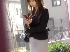 Busy attractive Asian hottie is typing text message during instant sharking
