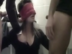 Blindfolded slut sucks the cock of 2 strangers in a public toilet