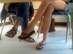 Beautiful feet dangling flip flops in class
