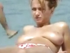 Oiling boobs on topless beach