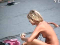 Voyeur beach nudist girl getting suntanned among bikini gals