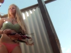 Young blonde with gorgeous tits changes clothes in a stall
